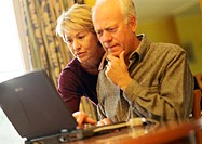 Mature couple, man using laptop, woman looking over shoulder