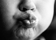Child puckering lips, close-up on mouth, b&w