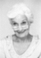 Senior woman looking over edge of glasses, close-up, portrait, blurred, b&w