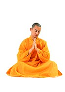 Buddhist monk sitting, meditating with hands together, front view