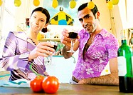 Couple standing in kitchen, raising their glasses