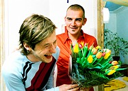 Two men smiling and laughing, one holding bouquet of flowers, portrait