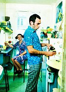 Couple in kitchen, woman sitting, man pouring wine