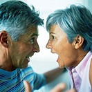 Mature man and woman having argument, side view