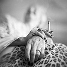 Mature woman´s hands holding cigarette, low angle view, b&w
