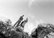 Two young people standing on rocks, low angle view, b&w