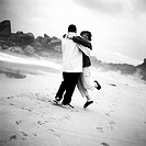 Couple smiling, hugging on beach, b&w