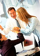 Two businesswomen playing at desk, businessman laughing