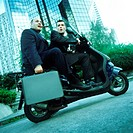 Two businessmen on motor scooter, one holding briefcase