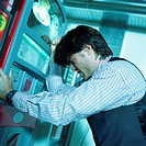 Businessman banging on vending machine, side view