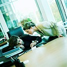 Young woman watching colleague sleeping at desk