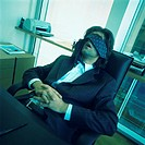 Young businessman sleeping at desk, tie covering eyes