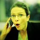 Woman using cell phone, making face, portrait