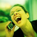 Woman laughing, using cell phone, portrait