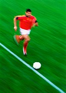 Soccer player running with ball, blurred