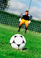 Soccerball in foreground, goal keeper in front of goal net, blurred in background