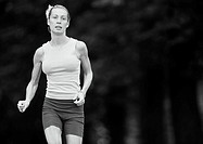 Woman in sports clothes running, three quarter length, b&amp;w