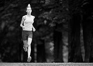 Woman running, full length, trees in background, b&amp;w