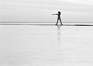 Woman exercising by the sea, b&amp;w