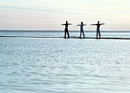 Three people exercising by the sea