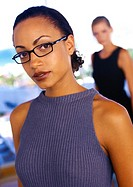 Businesswoman wearing glasses, second woman blurred in background, portrait