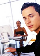 Businessman and businesswoman working at desks, man looking at camera