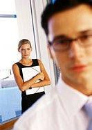 Businesswoman holding folder behind businessman
