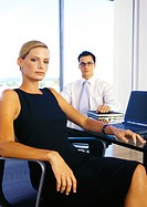 Businessman and woman sitting in office, portrait