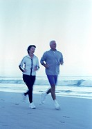 Mature man and woman running on beach