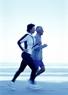 Mature man and woman running on beach, side view