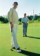 Two mature golfers on green, portrait