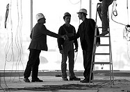 Men wearing hard hats, shaking hands