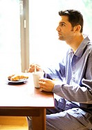 Man in pajamas having breakfast (thumbnail)