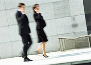 Businessman and woman using cell phones in street, full length, blurred motion