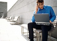 Man sitting on bench with cell phone and laptop