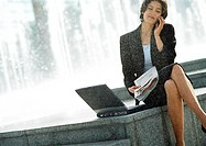 Businesswoman with cell phone and laptop computer, outdoors