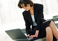 Businesswoman using laptop computer outdoors, close-up