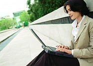 Businesswoman sitting with laptop computer outdoors