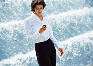 Businesswoman using cell phone in front of fountain