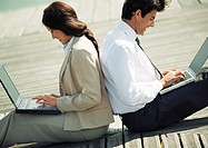 Businessman and woman back to back on ground with laptop computers on laps