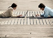 Man and woman lying on stomachs, outdoors, with laptop computers (thumbnail)