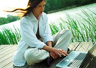 Woman sitting outdoors, using laptop computer