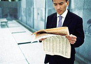 Businessman reading newspaper, waist up, long shot
