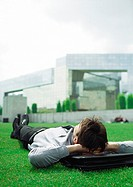 Businessman lying on grass with head on briefcase