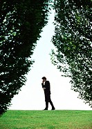Businessman in park, long shot, trees in foreground