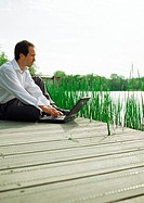 Man sitting outdoors with laptop computer