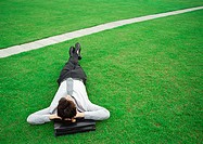 Man lying on grass, head on briefcase