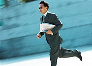 Businessman running outdoors