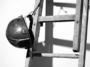 Hard hat tied to ladder, close-up, b&amp;w