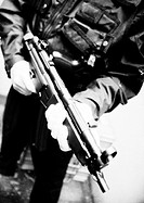 Man holding sub-machine gun, close-up, b&w